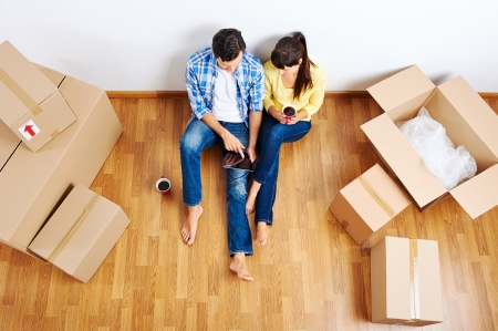 home moving: overhead view of couple moving in to new home and using wireless internet on tablet computer Stock Photo