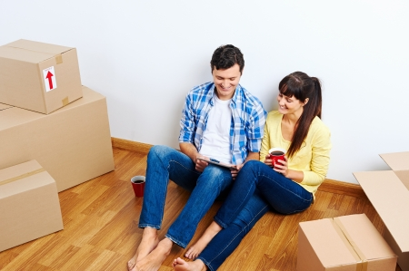 overhead view of couple moving in to new home and using wireless internet on tablet computer Stock Photo - 20863424
