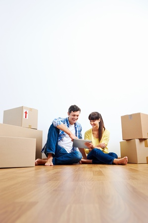 boxes: couple looking at tablet while moving into new home with boxes Stock Photo