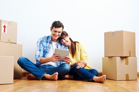 house property: couple looking at tablet while moving into new home with boxes Stock Photo