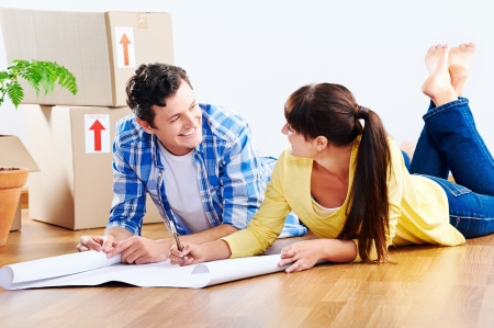 couple looking over plans to new house together lying on wooden floor photo