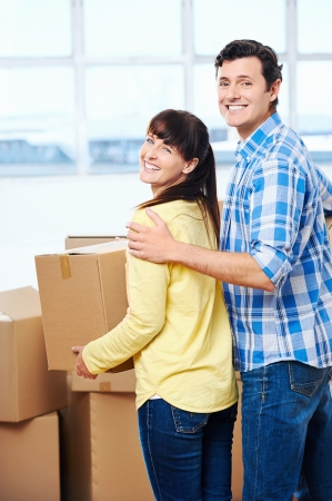 Happy couple carrying boxes moving into new home apartment house photo