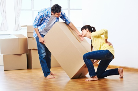woman back pain: back injury from carrying heavy box while moving home