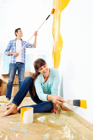 family moving house: renovation diy paint couple in new home painting wall