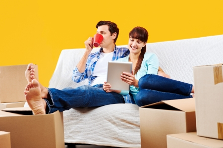 couple relaxing in new home with tablet computer on sofa couch Stock Photo - 20863486
