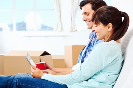 first move: couple relaxing in new home with tablet computer on sofa couch