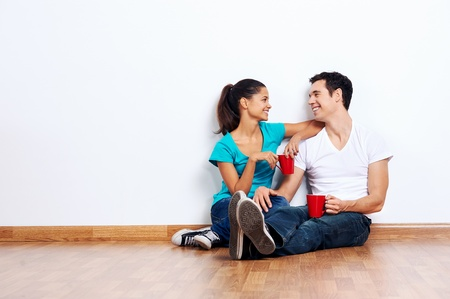 couple moving into empty new home sitting on floor together and drinking coffee Stock Photo - 20863525