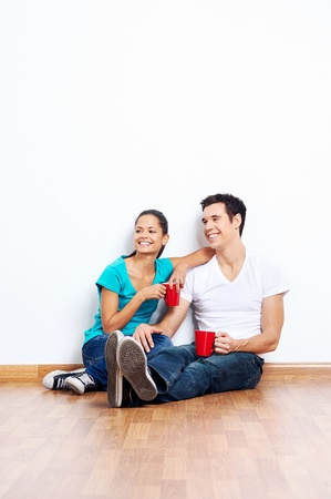 interracial love: couple moving into empty new home sitting on floor together and drinking coffee