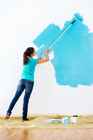 paintrush: woman painting wall in new home