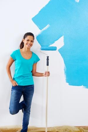 roller: Retrato de una mujer posando con rodillo de pintura en la nueva renovaci�n de apartamentos Foto de archivo