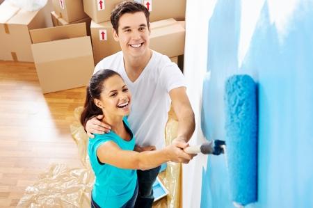 hombre pintando: vista a�rea de la pareja que se divierten renovaci�n de su nuevo hogar junto con pintura azul sobre un rodillo Foto de archivo