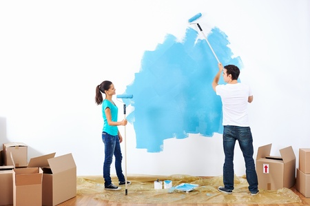 couple painting new home together with blue color happy and carefree relationship Stock Photo - 20761047