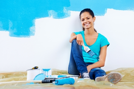 confident young woman portrait while painting new apartment renovating with blue color paint Stock Photo - 20863554