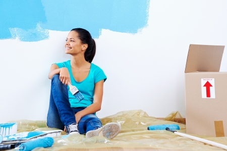 confident young woman portrait while painting new apartment renovating with blue color paint Stock Photo - 20850061