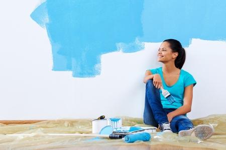 新しいアパートは、青いペンキの革新を描きながら自信を持って若い女性の肖像画 写真素材