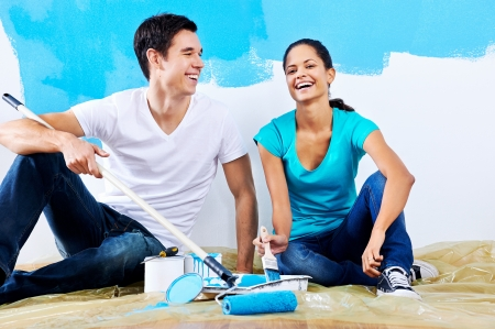 cute couple painting new home together portrait while sitting on wooden floor Stock Photo - 20761048