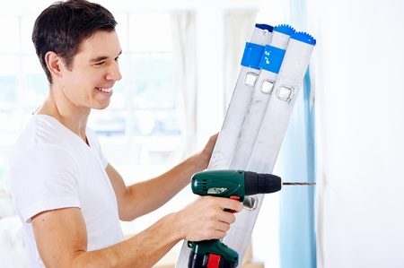 man doing diy drilling in new home after moving in standing on ladder photo