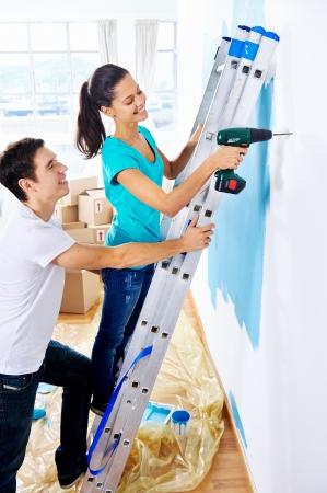 taladro: pareja de perforaci?n la pared haciendo bricolaje en el nuevo hogar despu?de mudarse a vivir juntos Foto de archivo