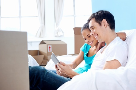 couple moving in together relaxing on sofa couch with laptop tablet computer and boxes photo