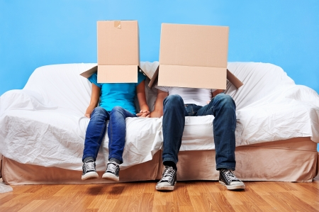 couple sitting on couch with moving boxes on head having fun\ together