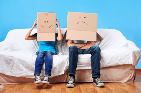 couple having fun: couple sitting on couch with moving boxes on head having fun together