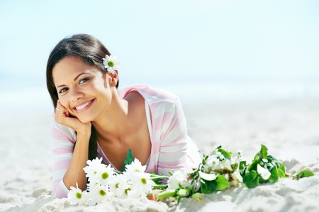 sea flowers: portrait of woman on beach with flowers relaxing in the sun