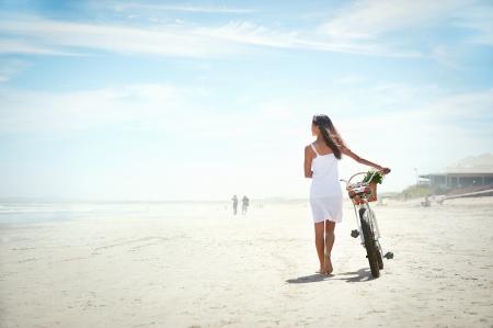 disfrutar: Mujer caminando con la bicicleta a lo largo de la playa de arena verano estilo de vida sin preocupaciones