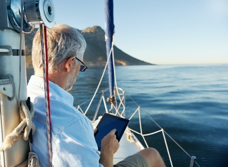 sailing man reading tablet computer on boat with modern technology and carefree retired senior successful lifestyle photo