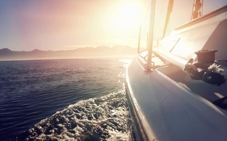 플레어 및 야외 생활로 일출 바다 물에 세일링 보트