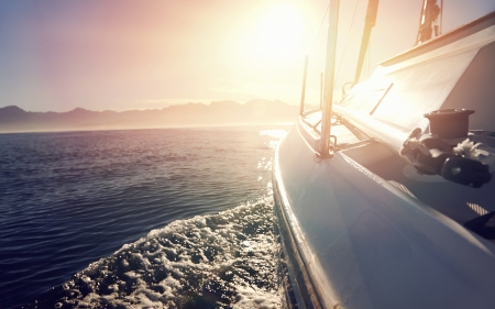 sailing: Sailing boat on on ocean water at sunrise with flare and outdoor lifestyle