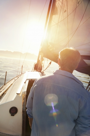 Sunrise sailing man with flare and boat on ocean photo