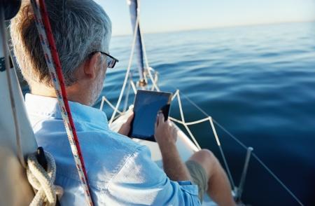 Segeln Mann liest Tablet-Computer auf dem Boot mit moderner Technologie und unbeschwerten pensionierter erfolgreichen Lifestyle Standard-Bild - 20904654