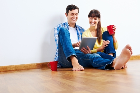 Couple moving in to new home and using wireless internet on tablet computer photo
