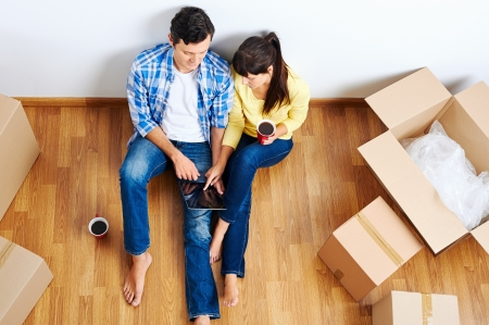 overhead view of couple moving in to new home and using wireless internet on tablet computer Stock Photo - 20940566