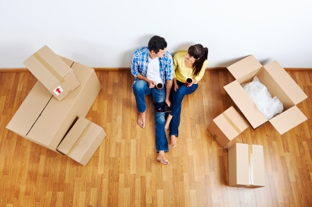 apartment house: overhead view of couple moving in to new home and using wireless internet on tablet computer Stock Photo