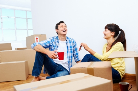 family moving house: couple celelbrating new home handing keys and moving boxes