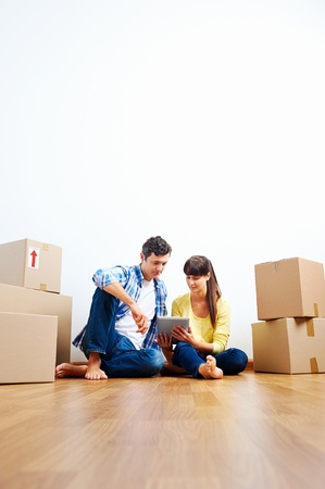 couple looking at tablet while moving into new home with boxes Stock Photo - 20943966