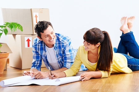 life plan: couple looking over plans to new house together lying on wooden floor Stock Photo
