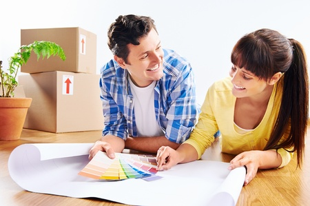 couple choosing paint colour from swatch in new home apartment together photo