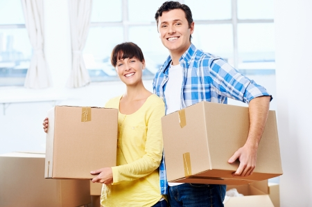 relocate: Happy couple carrying boxes moving into new home apartment house