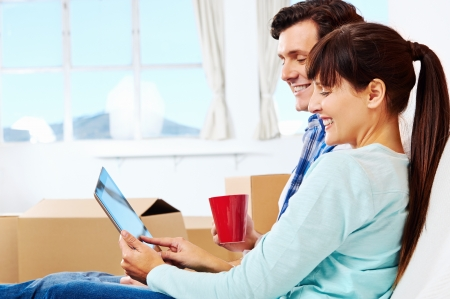 couple relaxing in new home with tablet computer on sofa couch photo