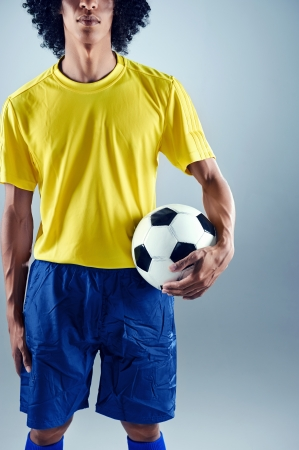 Portrait of Brazilian soccer football player with ball and national kit ready for the world cup photo