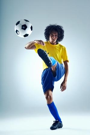 striker: soccer football kick striker scoring goal with accurate shot for brazil team  Stock Photo