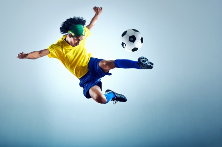 kicking ball: soccer football kick striker scoring goal with accurate shot for brazil team  Stock Photo