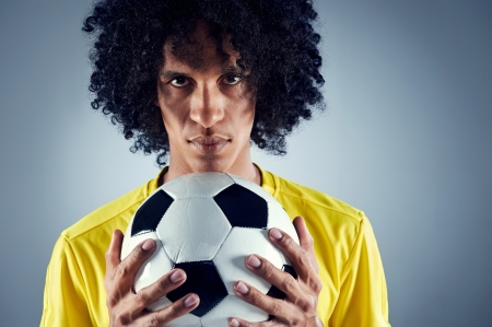 south american: Portrait of Brazilian soccer football player with ball and national kit