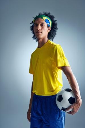 uniforme de futbol: Retrato del jugador brasileño de fútbol de fútbol con la bola y kit nacional