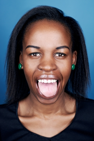 making a face: portrait of real funny face african woman on blue background Stock Photo