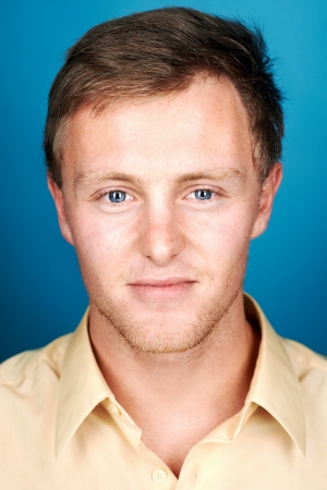 portrait of real man face looking at camera on blue background photo