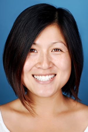 smiling portrait of real asian chinese woman happy on blue background Stock Photo - 22256377