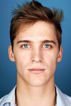 cerrar: retrato de verdadera cara del hombre mirando a la cámara sobre fondo azul Foto de archivo